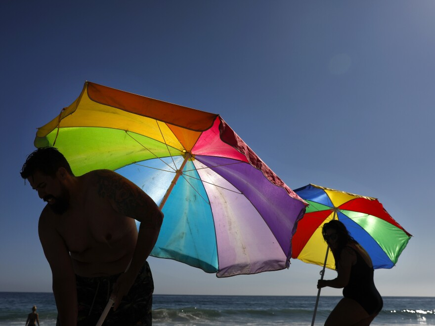 Mario Ramos (left) and wife Tally adjust their umbrellas in Laguna Beach, Calif. The state was among a number of places this summer that experienced their highest temperatures on record.