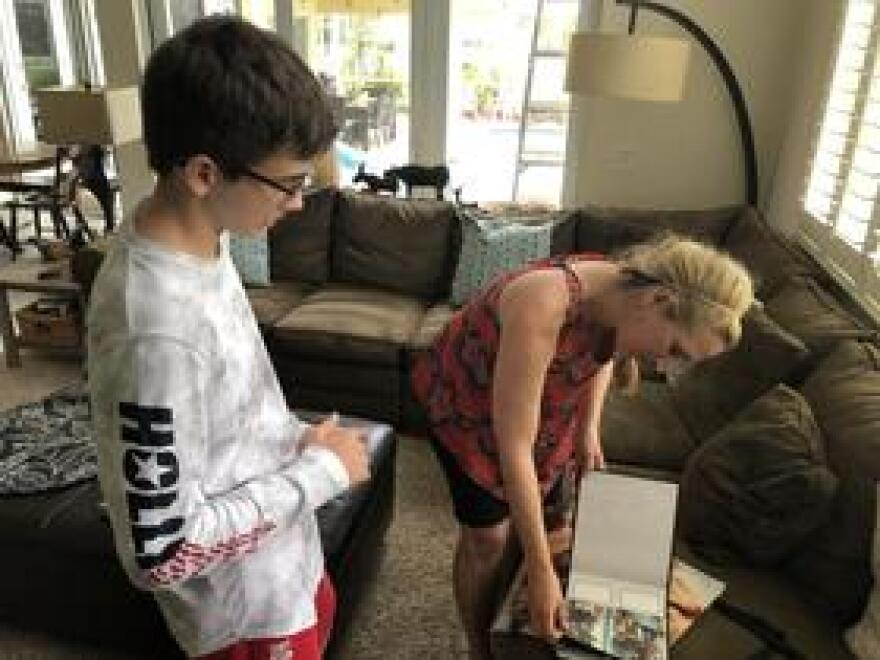 Marjory Stoneman Douglas High School sophomore William Olson and his mom, Lisa, flip through an album of photos showing the 15-year-old with therapy dogs at school after the shooting. The album was a gift from Debbie Beaudin, whose golden retriever Sammy developed a special bond with William.
