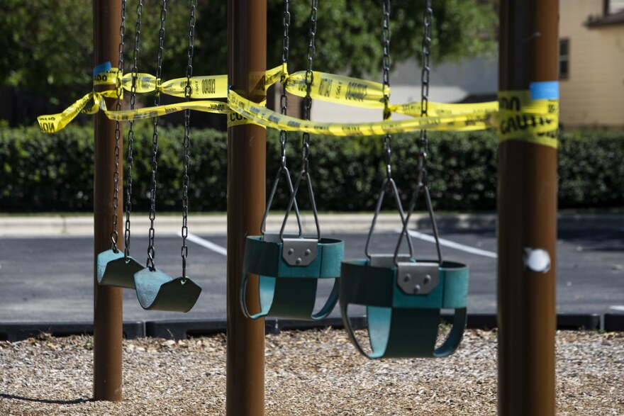 Caution tape surrounds playground equipment at McKinney Heights Park in South Austin. Park amenities in Austin were closed on March 28 to slow the spread of COVID-19.