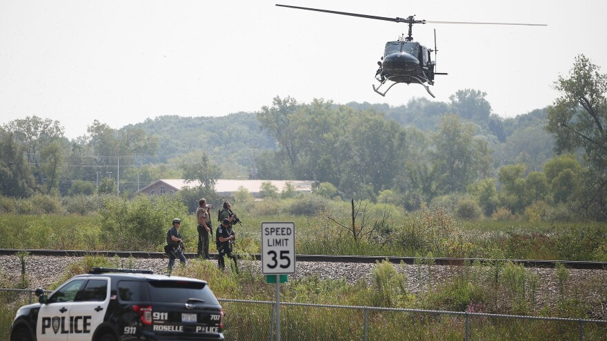 Police officers search an area around the Illinois city of Fox Lake, about 50 miles northwest of Chicago, for three suspects following the killing of a police officer early Tuesday.