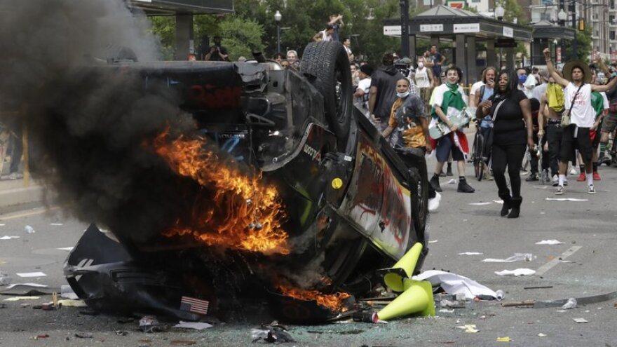 In this May 30, 2020, file photo, protesters demonstrate as a Salt Lake City police vehicle burns in Salt Lake City.