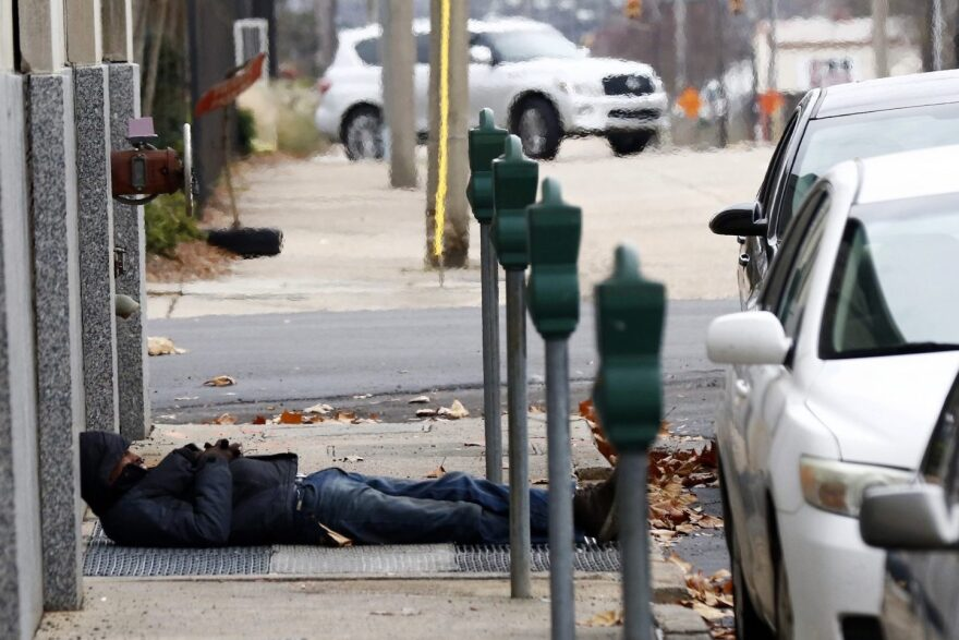 A man who is homeless takes advantage of the warm air coming from a sidewalk vent to stay warm in downtown Jackson, Miss., Wednesday, Dec. 27, 2017. (Rogelio V. Solis/AP)