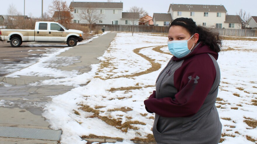 A woman wearing a blue mask and hoodie stands in a residential neighborhood, with a pickup truck parked in the background and snow on a grassy field behind her.