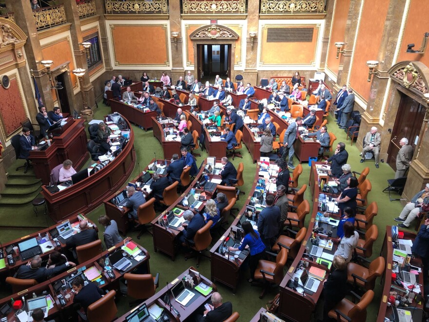 Photo of a legislative chamber, with people sitting at rows of wooden desks.