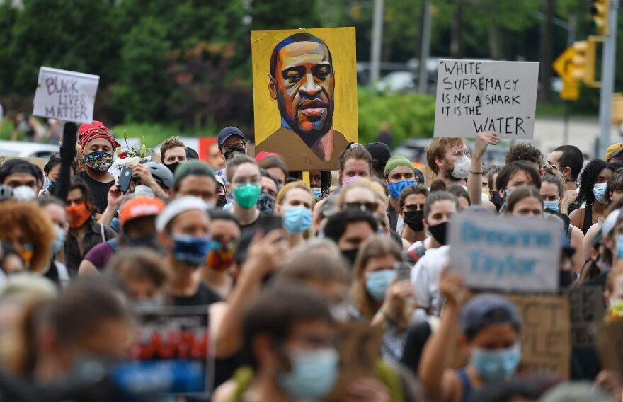 "A protester holds up a portrait of George Floyd during a ""Black Lives Matter"" demonstration in front of the Brooklyn Library and Grand Army Plaza on June 5, 2020, in Brooklyn, N.Y."