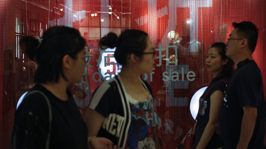 People pass a store in Beijing on Monday. The government's figures show that China's pace of economic growth in the second quarter was at its slowest in nearly three decades.