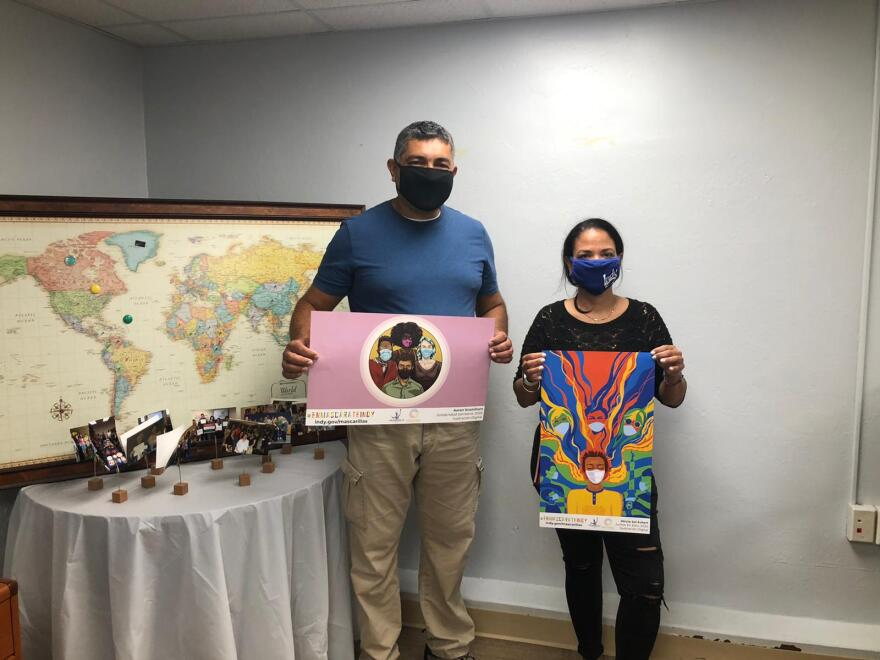 Two Natural Helper Specialists, Francisco Ruiz and Virna Diaz, collecting Mask Up posters to distribute to immigrant owned businesses for COVID-19 prevention.