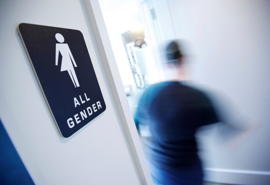A bathroom sign welcomes both genders at the Cacao Cinnamon coffee shop in Durham, N.C., on May 3.