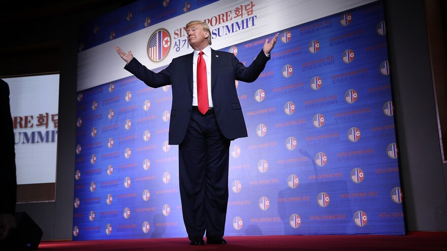 President Trump stands on the podium in Singapore with his arms outstretched and answers a final question from reporters. Back in the U.S., he was flexing his muscles in GOP primaries.