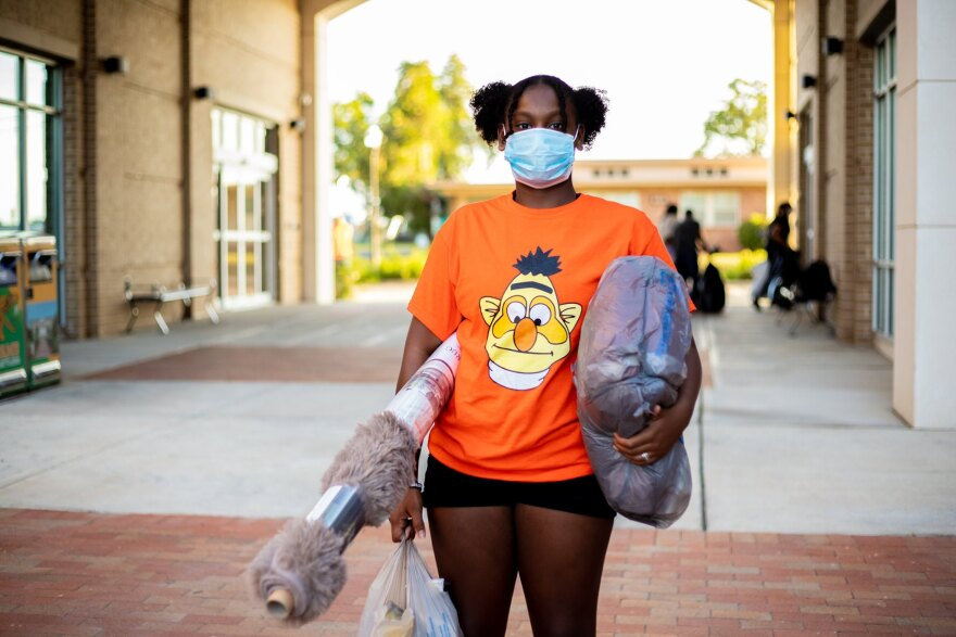 A woman in an orange shirt holds dorm supplies including a tan shag run. She is wearing a blue doctors mask.