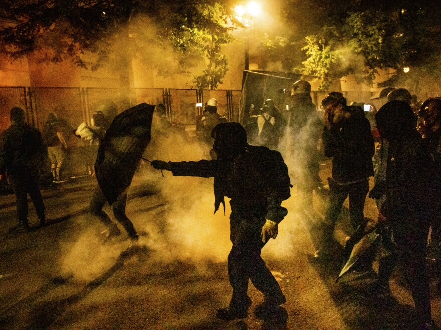 Protesters walk through chemical irritants deployed by federal agents in Portland, Ore. The Justice Department inspector general says he is investigating federal officers' roles in responding to protests in Portland and Washington, D.C.