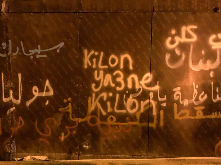 "Graffiti showing the words ""<em>Kilon Ya3ne Kilon</em>,"" one of the loudest chants being heard in recent days in Lebanon. It means ""All of them means all of them!"""