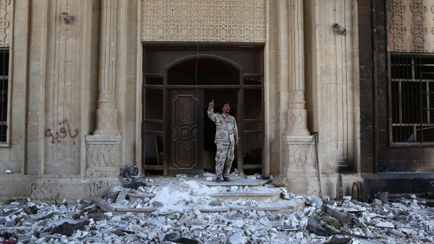 A Shiite militia fighter stands in front of a damaged building in Tikrit, Iraq, in April, just days after Islamic State fighters were driven out. Many of the city's Sunni residents have now returned, but the armed Shiite groups remain. For now, the Sunnis and Shiites are mostly getting along.