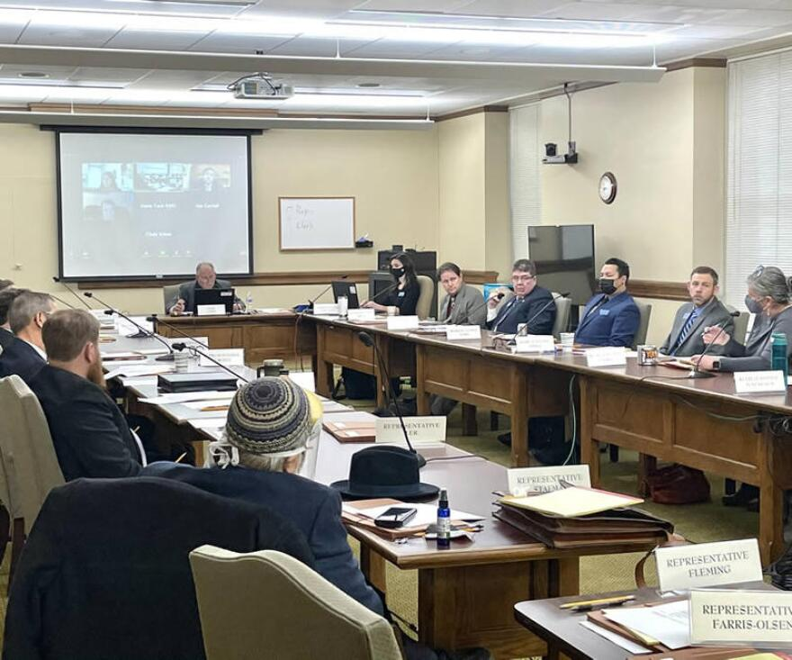 Members of the Montana House Judiciary Committee sit around a U-shaped conference table. A few wear masks but most don't.