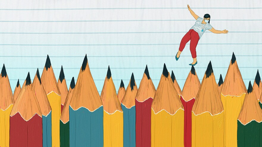 A masked teacher balances on the tip of sharpened pencils.
