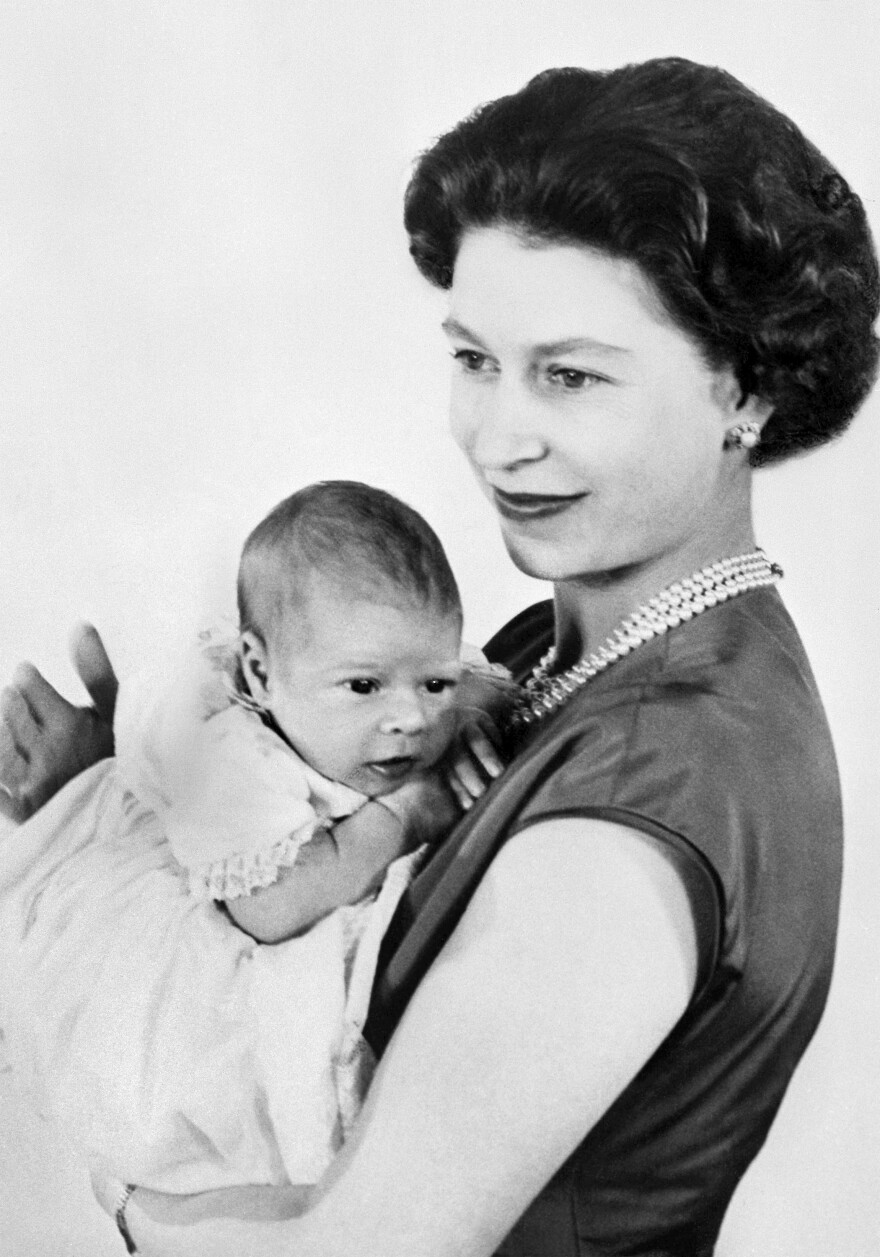 One of the first pictures of Prince Andrew, shown in the arms of his mother, Queen Elizabeth II. He was born in 1960.