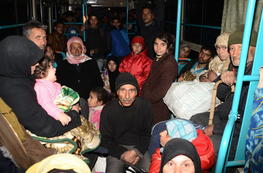 Syrian families from various eastern districts of Aleppo are evacuated by bus through Sheikh Maqsud, a Kurdish-controlled enclave between the government-held west of Aleppo and the east, on Sunday, as Syrian pro-government troops continue their advance toward rebel-controlled districts.