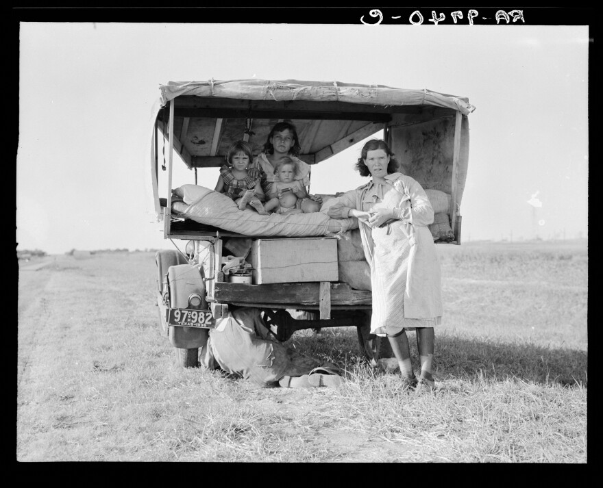 "A family traveling between Dallas and Austin, Texas. ""The people have left their home and connections in South Texas, and hope to reach the Arkansas Delta for work in the cotton fields,"" Lang wrote in her notes. ""Penniless people. No food and three gallons of gas in the tank. The father is trying to repair a tire. Three children. Father says, 'It's tough but life's tough anyway you take it.' """
