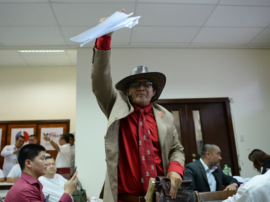 "Ephraim Defino waves his candidacy certificate after filing as a presidential candidate at Manila's election commission. So-called ""nuisance"" candidates are a staple of the Southeast Asian nation's chaotic democracy."