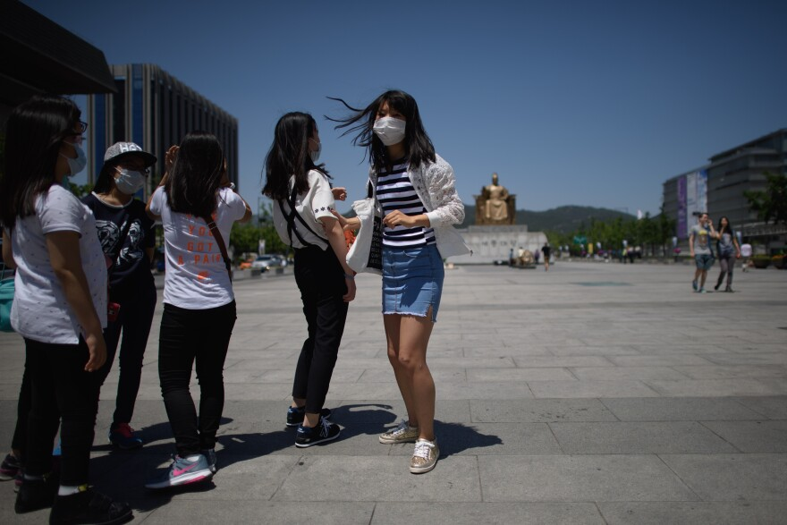 A student wearing a face mask stands in a public square in Seoul on June 3. More than 200 primary schools shut down as South Korea has struggled to contain an outbreak of the MERS virus.