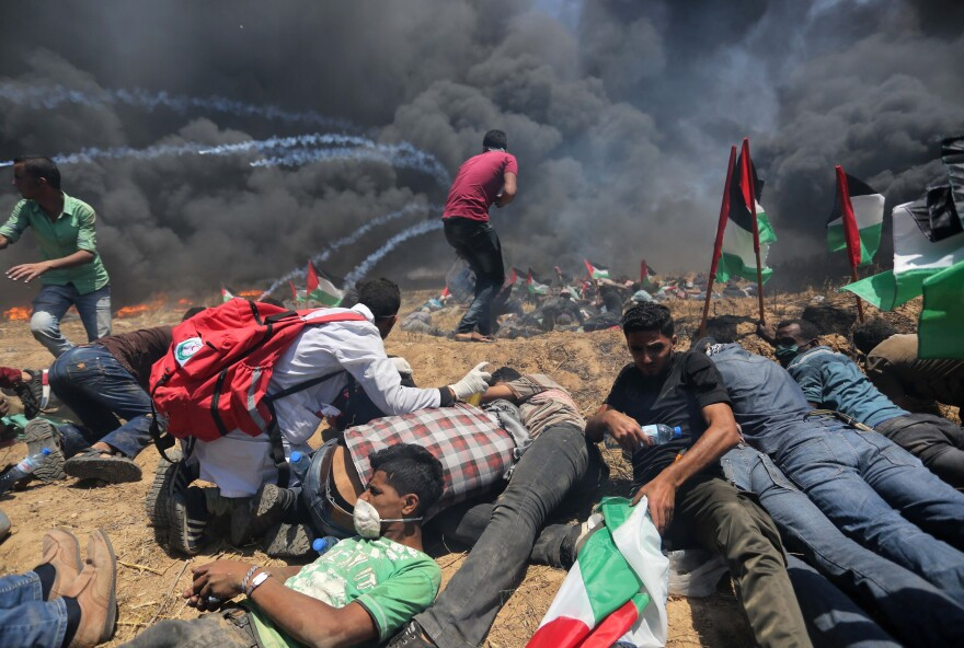 Palestinians set tires on fire, as Israeli soldiers attempt to prevent protesters from breaking through the Gaza-Israel border. The demonstration marked the 70th anniversary of Nakba, or catastrophe, a commemoration of the displacement of hundreds of thousands of Palestinians in the war surrounding Israel's creation.