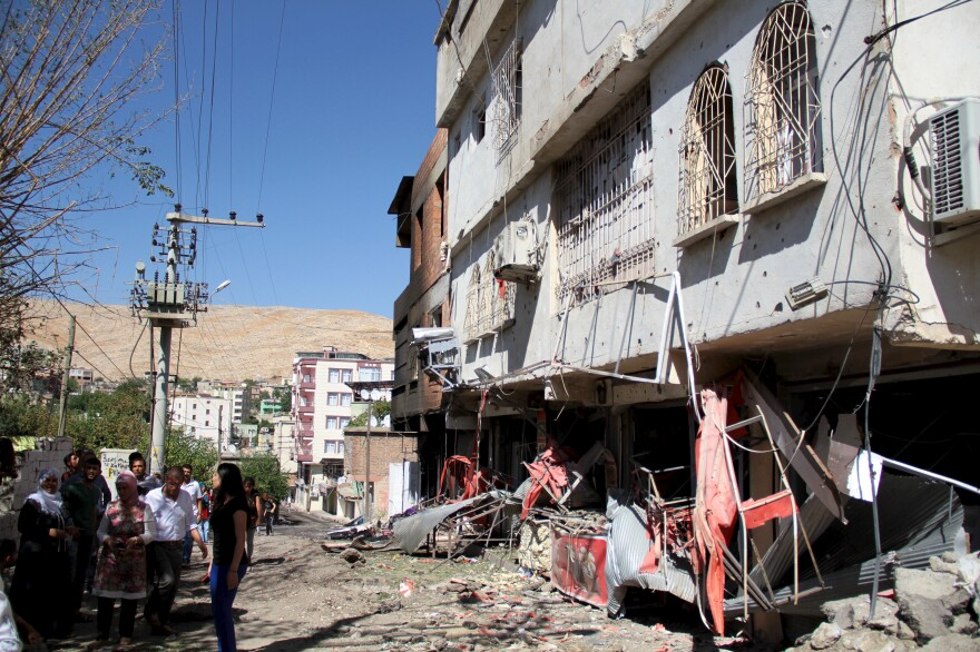 People gather outside a damaged building after clashes in Silvan between Turkish security forces and members of the Kurdistan Workers Party (PKK) youth wing last week.