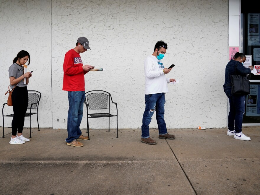 People who lost their jobs wait in line to file for unemployment benefits at an Arkansas Workforce Center in Fayetteville, Ark., on April 6.
