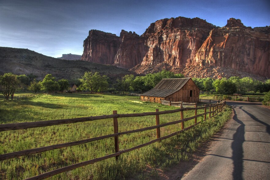 A farmhouse sits between a lush green field and red-rock cliff-face.