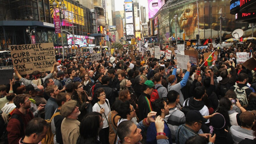 <p>Demonstrators protest in New York's Time Square on Saturday. Thousands of people took to the streets in cities across the world, inspired by the Occupy Wall Street protests against economic inequality.</p>