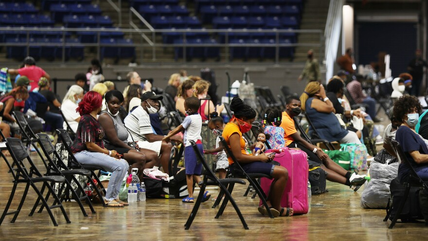 People wait to board buses Tuesday in Lake Charles, La., as they prepare to be evacuated before Hurricane Laura's arrival.