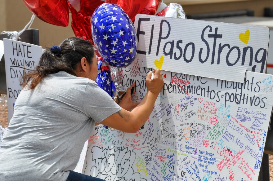 A woman leaves a message at a memorial for victims of the El Paso shooting