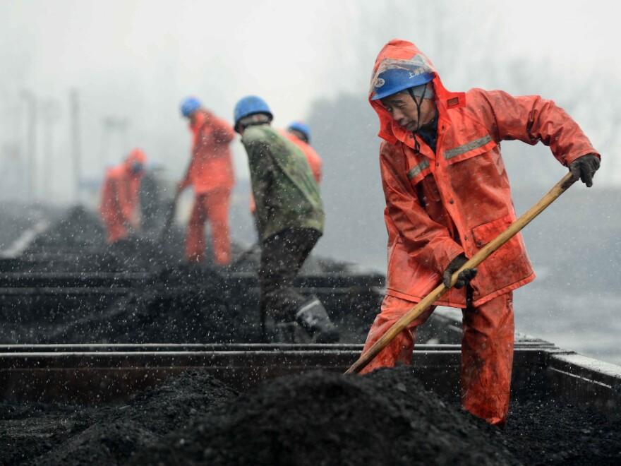 Workers load coal onto rail cars during snowfall at a railway station in Jiujiang, China, last year.