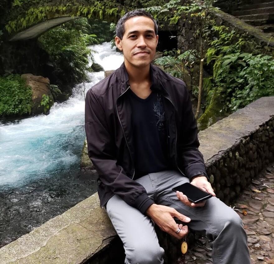 Veteran Sergio Alfaro sits in front of a river.