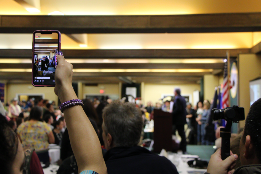 A woman holds up a smart phone that is recording a man standing at a podium in front of her.