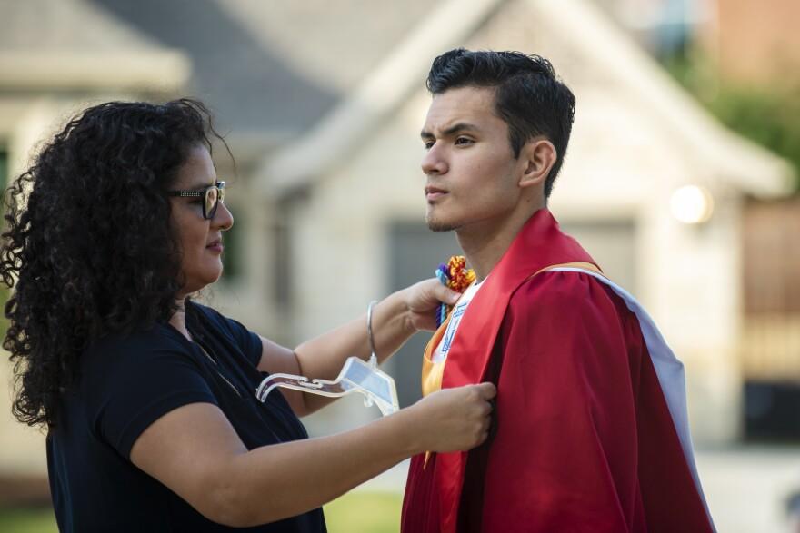 Xochitl Ortiz, de 47 años, a la izquierda, ayuda a su hijo Izcan Ordaz a probarse su traje de graduación frente a su casa en Keller, Texas, el 28 de mayo de 2020.