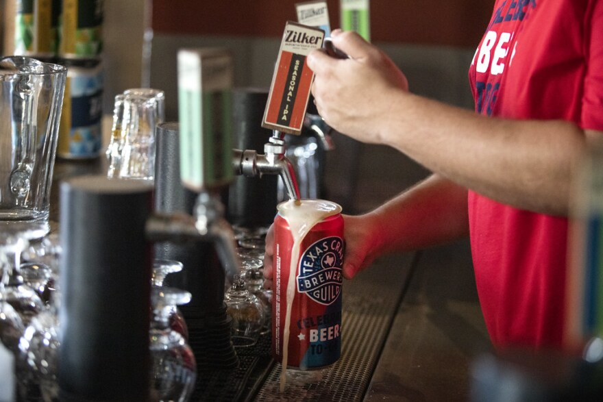 A Zilker employee pours a beer