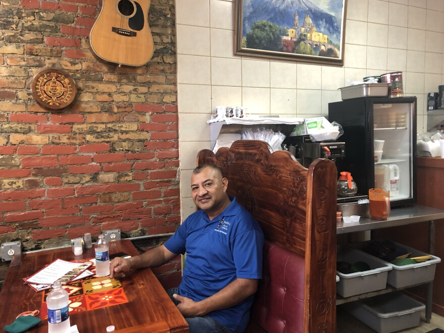 Pablo Maldonado Chávez se sienta en una mesa de madera en su restaurante, Pablo's Old Town Mexican Restaurant.  Maldonado Chávez vistiendo un polo azul.  En la mesa del stand hay dos botellas llenas de agua, un menú y una mascarilla de tela.