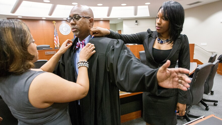 Judge Adrian Adams is helped with his robe by his daughters during a robing ceremony Friday in Gretna, La. Adams won a race for 24th Judicial District Court in November behind a campaign that raised a modest $22,350, including several four-figure donations from attorneys and law firms. Louisiana law, like Florida law, bars judicial candidates from personally soliciting campaign contributions.