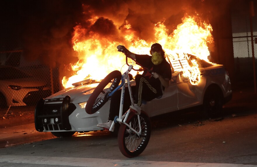 In this May 30, 2020, file photo, a protester on a bicycle rides past a burning police car during a demonstration next to the city of Miami Police Department in Miami. Protests were held throughout the country over the death of George Floyd, a black man who was killed in police custody in Minneapolis on May 25