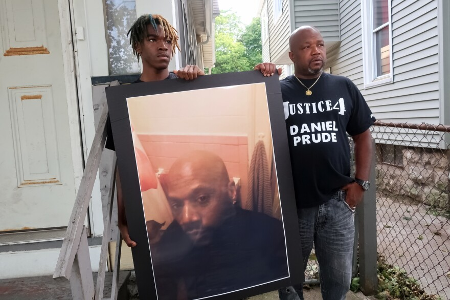 "Family members Armin Prude (left) and Joe Prude stand with a picture of Daniel Prude in Rochester, N.Y., Thursday, Sept. 3, 2020. While suffering a mental health crisis, Prude, 41, suffocated after police in Rochester put a ""spit hood"" over his head while being taken into custody. He died March 30 after he was taken off life support, seven days after the encounter with police."