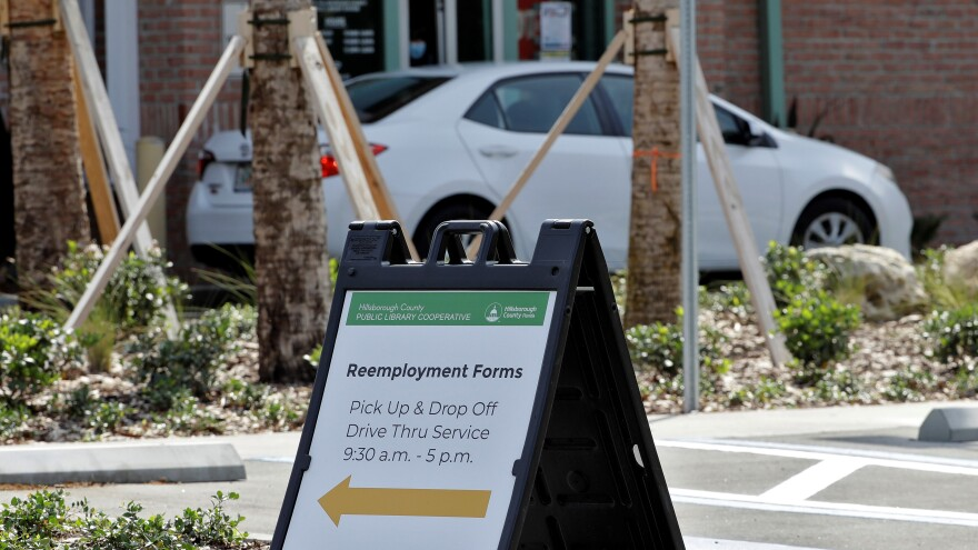 A car stops to pick up reemployment forms at the Jimmie B. Keel Regional Library in Tampa.