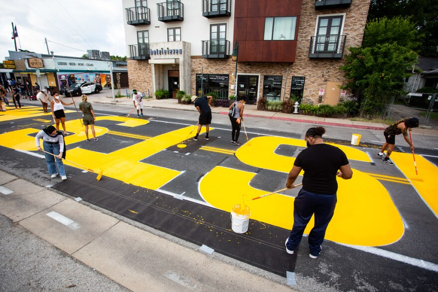 """A team of artists and volunteers paints the words """"Black Artists Matter"""" in yellow along East 11th Street."""