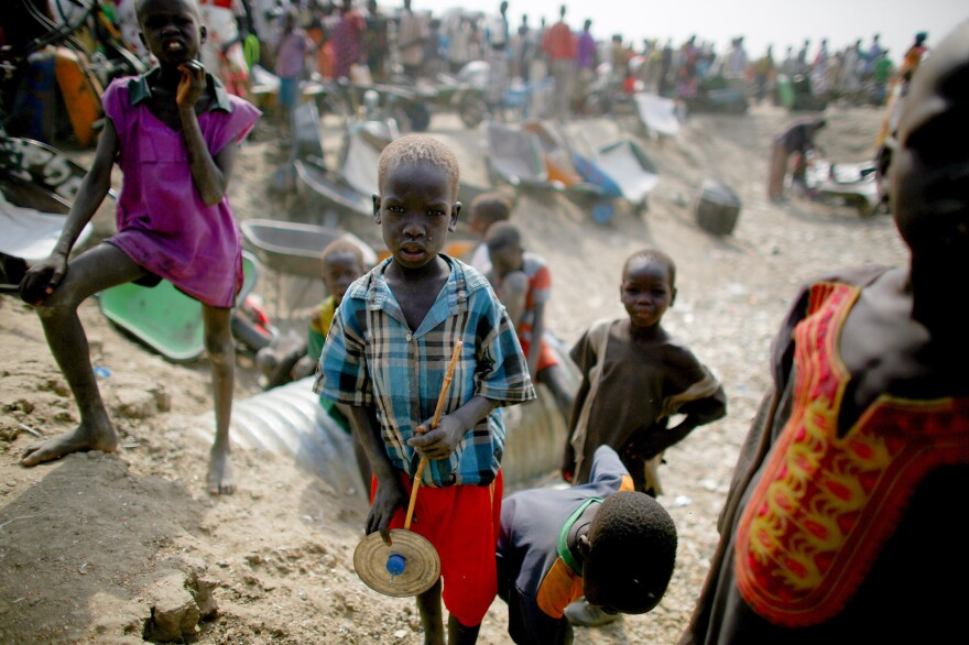 Kids play in front of a line for food rations at the camp. The 120,000 residents — the majority of whom are children — depend on distributions from the U.N. World Food Program.