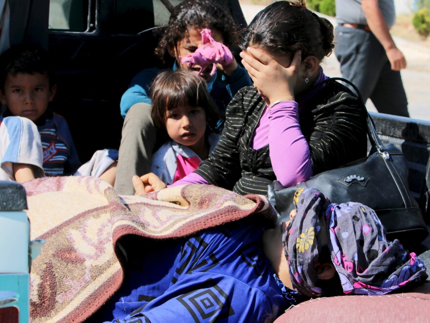 Civilians, reportedly wounded by fighting in Kobani, wait with their relatives to cross into Turkey at the Syrian-Turkish border crossing of Tel Abyad, Syria, on Thursday.
