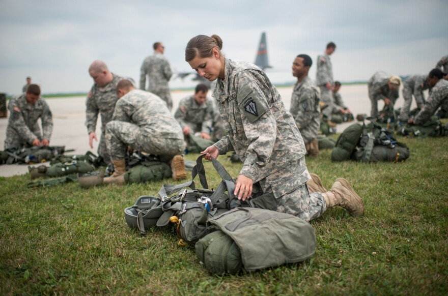Indiana Army National Guard Pvt. Trea Colon inspects her equipment during a field training exercise at Camp Atterbury and Muscatatuck.