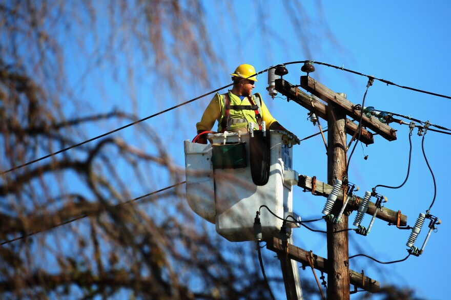 A worker repairs electrical lines in Plainview, N.Y., after Superstorm Sandy in 2012. A proposed plan to overhaul the state's power grid could help the system better withstand severe weather and enable energy to be stored and managed more efficiently.