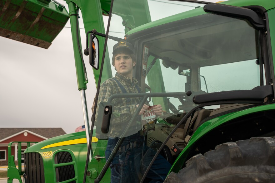 Alec Langley, a 15-year-old sophomore, works as a farmhand on a 1,000-acre corn and soybean farm, alongside his dad. Alec's tractor is a borrowed John Deere.