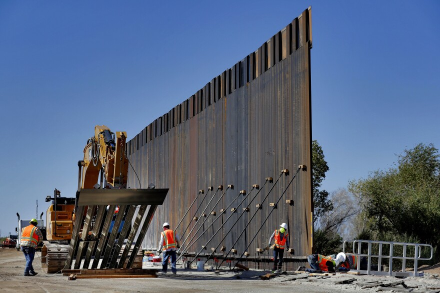 Government contractors erect a section of Pentagon-funded border wall along the Colorado River in Yuma, Ariz. Defense officials say the Department of Homeland Security has asked the Pentagon to fund the construction of 270 miles of border wall this year.