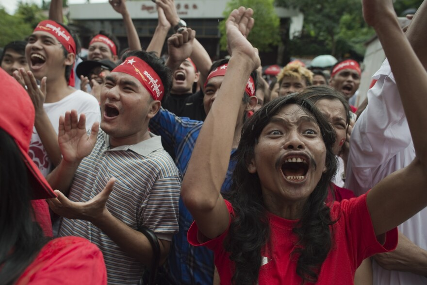 Supporters of Myanmar opposition leader Aung San Suu Kyi celebrate as they hear the first official results of the elections on a giant screen outside the National League for Democracy headquarters in Yangon on Monday.