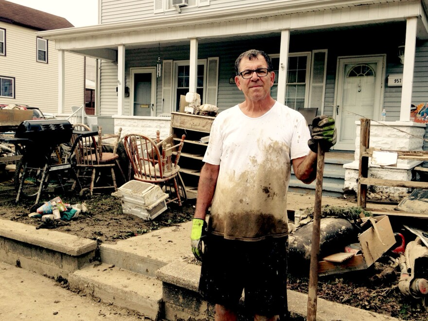 Arthur Quattrocchi stands in front of his son's house Monday, Aug. 1, 2016, in Follansbee, W.Va., joking about having a yard sale. The town was flooded during severe storms that hit West Virginia's Northern Panhandle on Saturday, July 30.